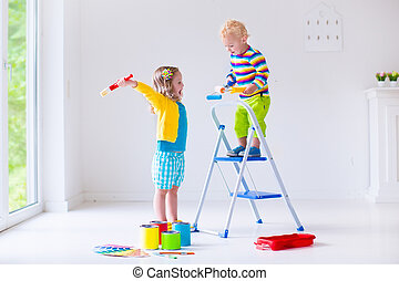 Children painting walls at home - Family remodeling house....