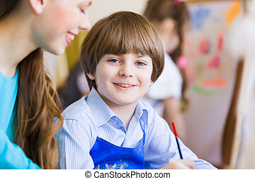 Children painting with teacher