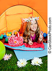Children peace hand sign girl lying in camping tent