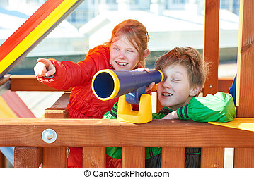 Children plaing on playground with telescope