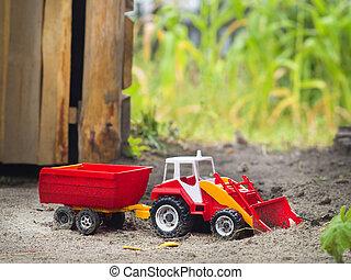 Toy tractor - Children plastic machine in the sandbox. Toy...