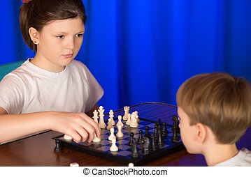 Children play a board game called chess. - Children spend a...