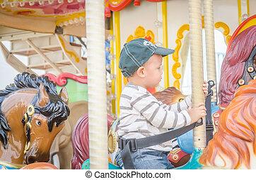 Children play carousel horse