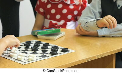 Children play checkers at a kindergarten. Close-up -...