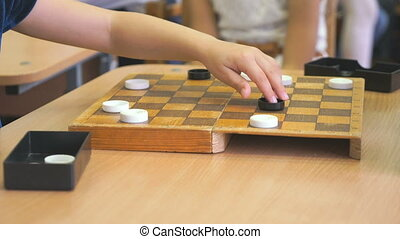 Children sit at the table and play checkers at the kindergarten. Close-up