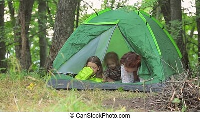 Children play in a green tent, set in a clearing in the forest. Close the grid in the tent.