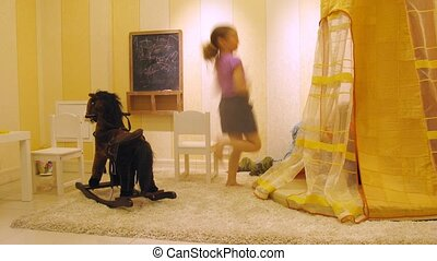 Children play in playroom with toy horse near blackboard