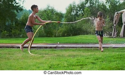 Children play in summer with water pouring from a hose