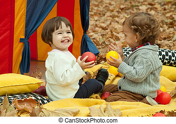 Children play in the park and eating apple.