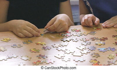Children play intellectual game collecting puzzles -...