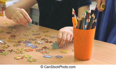 Children play a intellectual game collecting puzzles at the table at the kindergarten. Close-up