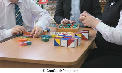 Children sit at the table and play intellectual games at the kindergarten