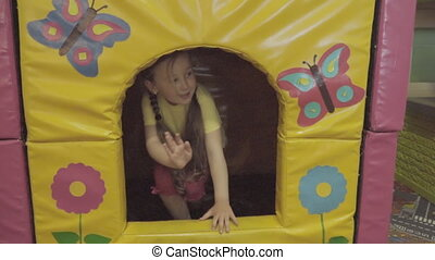 Children play near a toy house