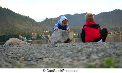 children play on the banks of the river