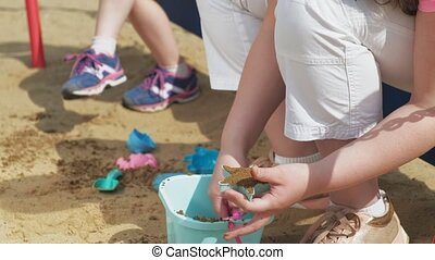 Children play on the sandbox outdoors. Sculpting sand...
