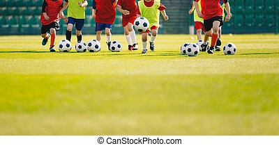 Children play soccer at grass sports field. Football training for kids. Children running and kicking soccer balls at soccer pitch. Soccer background with copy space on the bottom