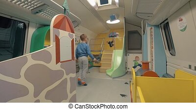 HELSINKI, FINLAND - JANUARY 05, 2017: Boy coming to the train carriage with play space. Playroom equipped for children fun and safe leisure during the journey from Helsinki to Rovaniemi
