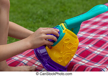 Children play toys on a plaid blanket on the grass in the garden