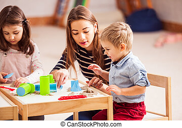 Children play with kinetic sand in the kindergarten
