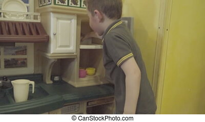 children play with small kitchen furniture