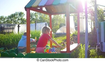 Children play with toys in the sandbox. Summer sunny day