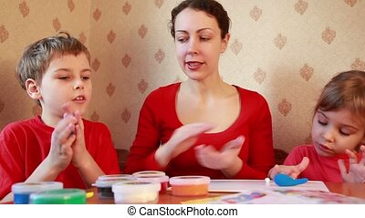 Children play with woman, sculpt plasticine
