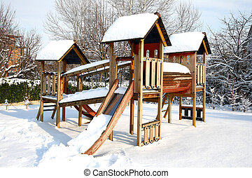 Children Playground In Public Park Covered With Winter Snow