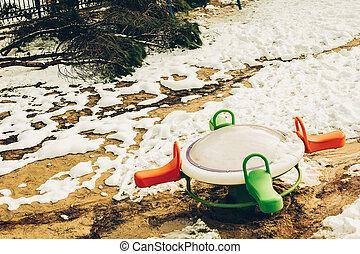 Children playground under snow in winter