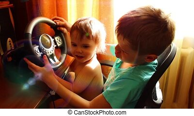 Children playing a computer game with the wheel