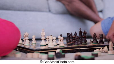 Children Playing a Game of Chess - Close-up of siblings...