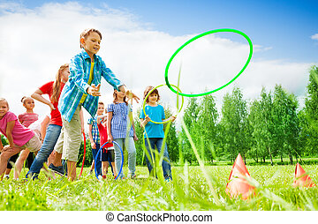 Children playing and throwing colorful hoops on cones while ...