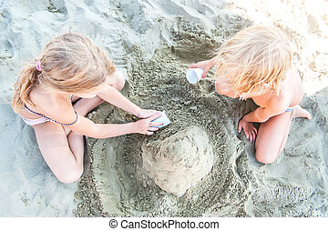 Children playing at the beach with sand