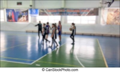 children playing basketball match blurred background....