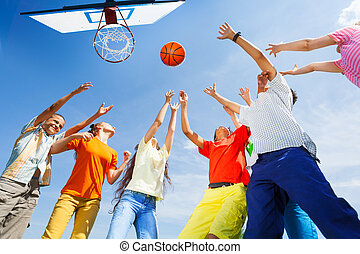 Children playing basketball with a ball up in sky
