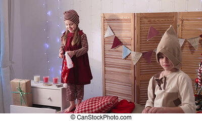 Children playing by Christmas tree, girl wearing a hat