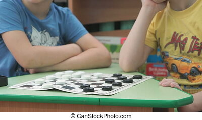 Children sit at the table and play checkers games at the kindergarten