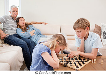 Children playing chess in front of their parents