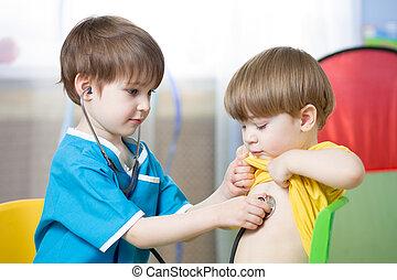 Children playing doctor in playroom or kindergarten - ...