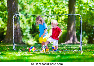 Children playing football outdoors - Two happy children...