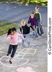 Children playing hopscotch - Children lined up on driveway,...