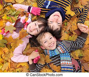 Portrait looking down on three smiling young children lying in Autumnal leaves.
