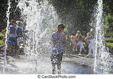 children playing in fountain - Happy children playing in a...