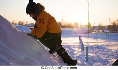children playing in snowy mountains, to climb to the top. At sunset