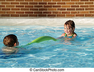 children playing in swimming pool - little girl and boy...