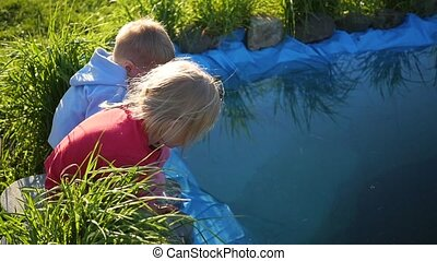 children playing in the Park near the pond. Summer Sunny day