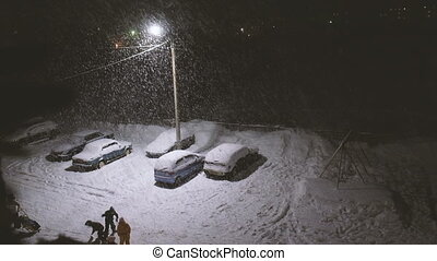 Children playing in the street in heavy snow under the streetlights