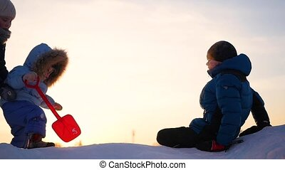 children playing in winter at sunset