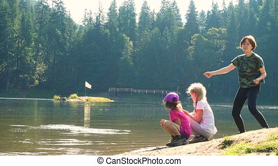 children playing near the lake - children playing and having...