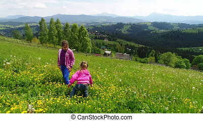 Children playing on a flowering lawn against the backdrop of the Carpathian Mountains