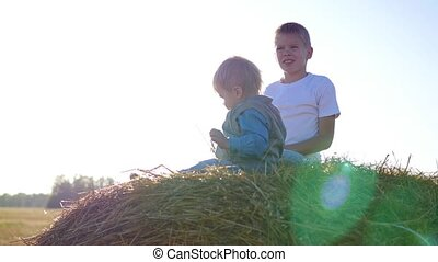 children playing on a haystack in the sun